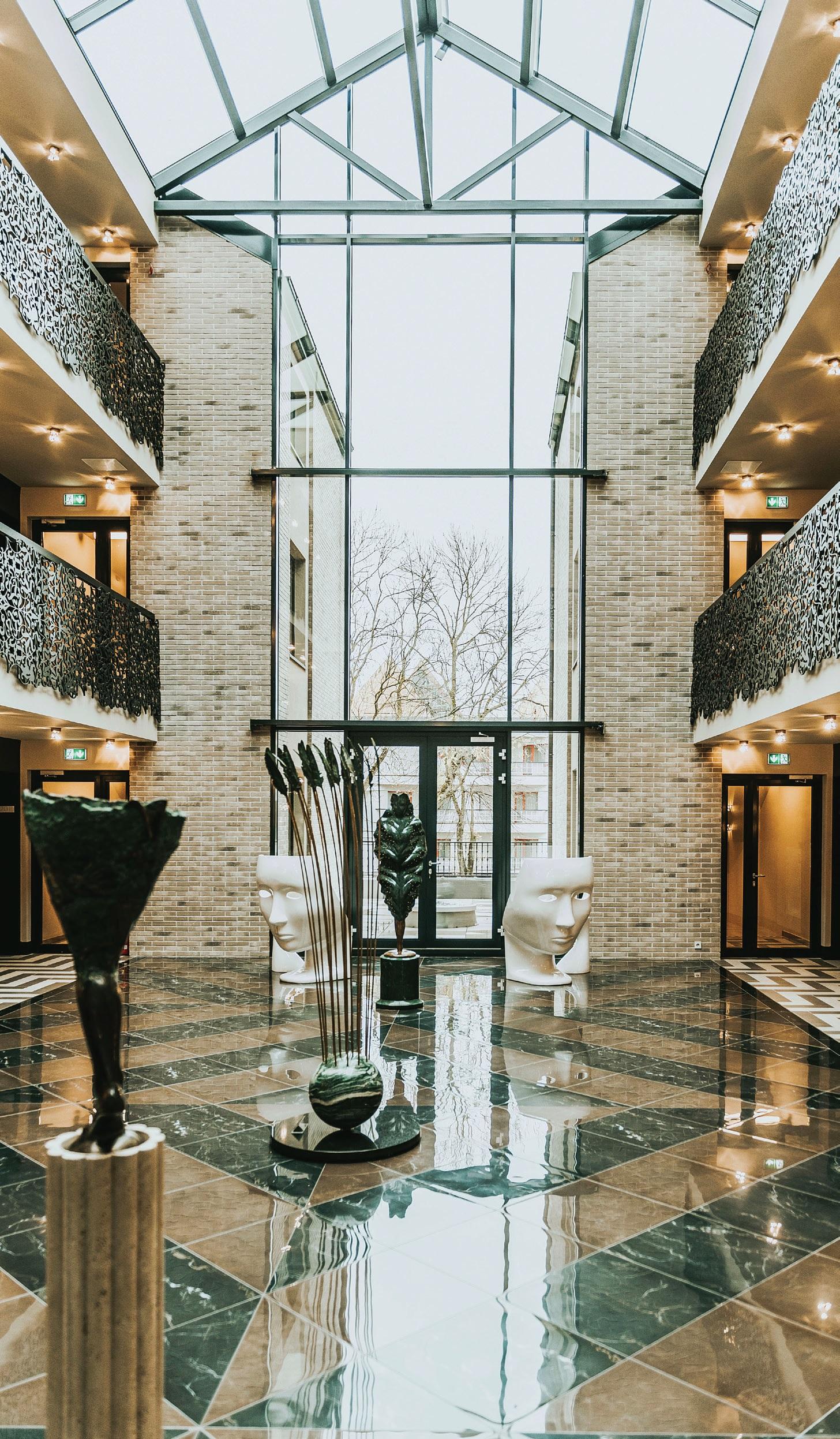 Atriumo grindų piešinys – tarsi Amsterdamo kanalų vanduo. Erdvę puošia viešbučio meno mecenatų kūriniai