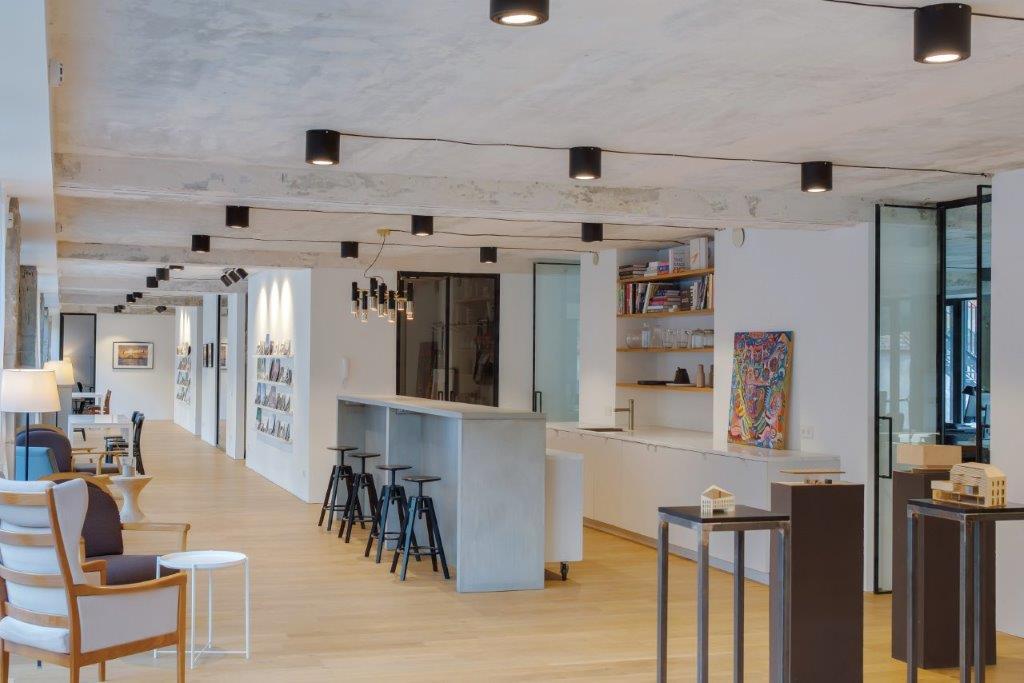 """Virtuvės zoną bendroje erdvėje puošia tapybos darbai ir atviros knygų lentynos (""""Do Architects"""" projektas)"""