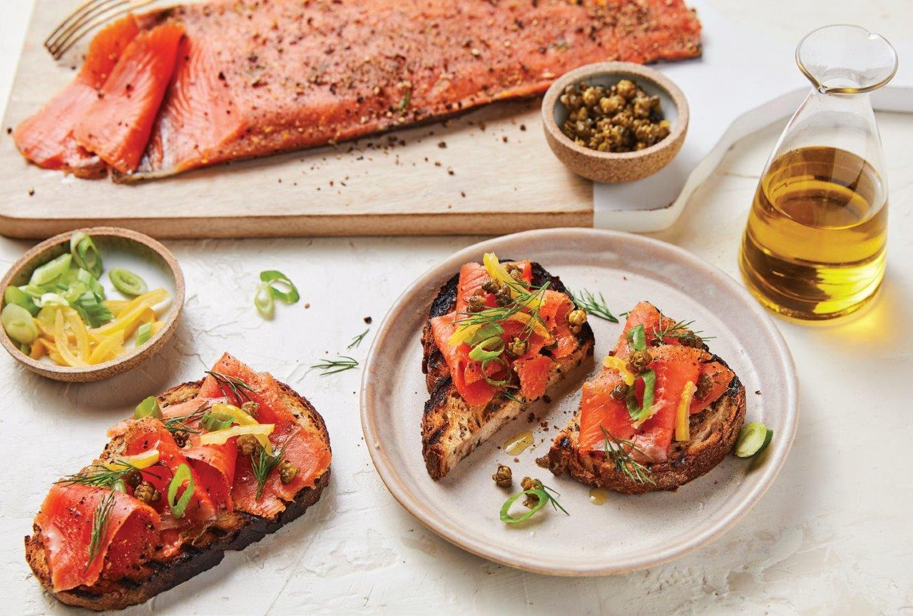 Rūkyta Aliaskos lašiša ant keptos ruginės duonos su pakepintais kaparėliais, svogūnais, konservuota citrina ir krapais